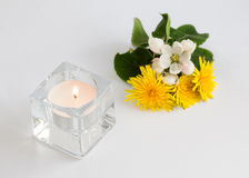 White candle and bouquet of bright flowers. White candle in glass candle holder and bouquet of bright flowers isolated on white background Stock Photo