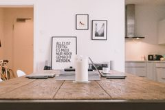 White Candle on Brown Wooden Table Beside White Wall Stock Photo