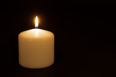 White candle burning against a black background Royalty Free Stock Images