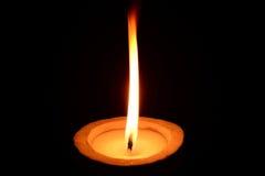 White candle burning on a black background Stock Photos