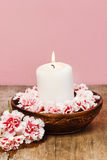 White candle among carnation flowers Royalty Free Stock Photos