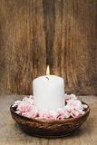 White candle among carnation flowers Stock Photo