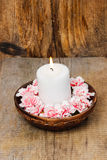 White candle among carnation flowers Royalty Free Stock Photo