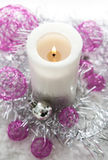 White candle and Christmas decorations around Royalty Free Stock Photography