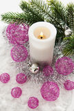 White candle and Christmas decorations around Stock Images