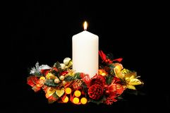 White candle and Christmas decorations. Royalty Free Stock Photo