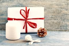 White candle, Christmas present and small bauble. royalty free stock photos