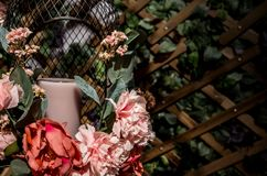 A white candle in decorated bird cage from artificial flower stock images