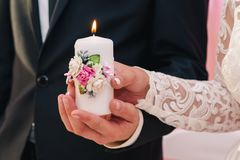 White candle with a decoration of flowers in the hands of the newlyweds. The concept of the family hearth stock image