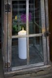 White candle in decorative lantern with flowers in the backgroun Royalty Free Stock Photos