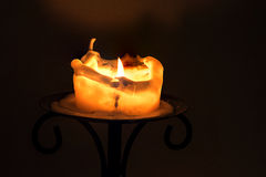 White candle with flame and melting wax on an iron candlestick a Stock Photo