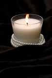 White Candle in Glass. With pearls on black fur Stock Photo