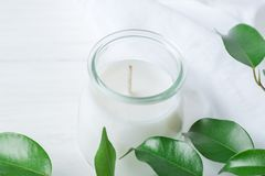White Candle in Glass Jar Fresh Tree Branches with Tender Green Leaves on Wood and Cotton Linen Fabric Background Royalty Free Stock Photo