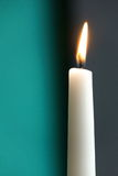 White candle with grey and turquois background. Close-up view stock images