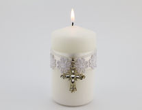 White candle with lace, ribbon and Christian cross pendant isola Royalty Free Stock Image