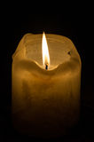 White candle. A large candle with its lighting flame on a dark background Stock Photography
