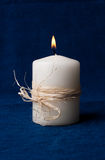 White candle that is lit on a dark blue background Royalty Free Stock Images