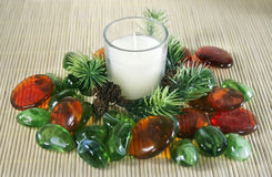 White candle with pine branch and colorful stones. Royalty Free Stock Photography