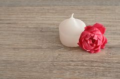 A white candle with a pink rose. On a wooden background Royalty Free Stock Images