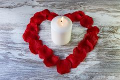 White candle in a red heart made with petals on rustic white background with copy space. stock photos