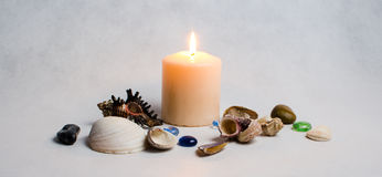 White candle, seashells and colored pebbles Royalty Free Stock Photography