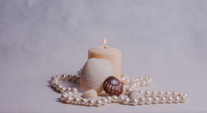 White candle, shells and pearl beads Royalty Free Stock Photo