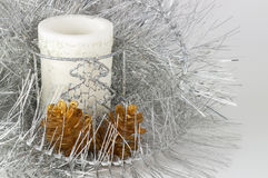 White candle in the silver tinsel Royalty Free Stock Photography