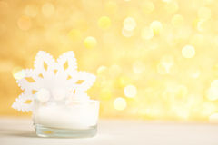 White candle and snowflake on golden bokeh background. Focus in candlewick. minimalistic holiday concept, text space Royalty Free Stock Photo