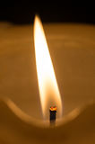 White candle. The warm and lighting flame of a candle on a dark background Royalty Free Stock Photo