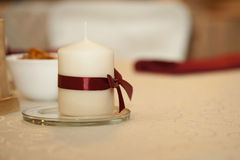 White candle on a white table Stock Photo