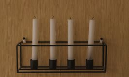 White candles on a black geometric stand stock photography