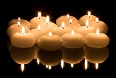 White candles on a black reflecting background Stock Image
