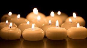 White candles on a black reflecting background Royalty Free Stock Photography