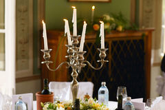 White candles burn standing in the old steel candleholder on a d. Inner table royalty free stock photo