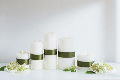 White candles burning with flowers on  white shelf Royalty Free Stock Photo