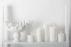White candles burning on a  shelf Royalty Free Stock Photos