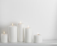 White candles burning on  white shelf Stock Photography