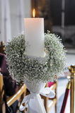 White candles and carnations flower wedding decoration in a chur Stock Photo