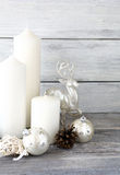 White candles with Christmas balls and decor deer on the boards Royalty Free Stock Images