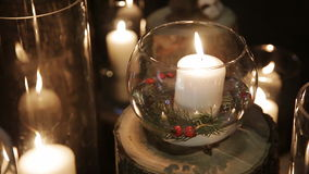 White candles in glass vases. Standing on a wooden platform at night stock video