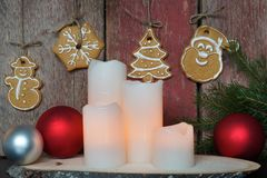 White candles near a red wooden wall with Christmas cookies and fir branches.  Royalty Free Stock Photos