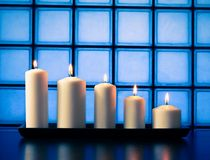 White candles on wood table Stock Photos