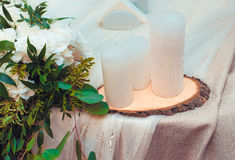 White candles on a wooden support royalty free stock photo