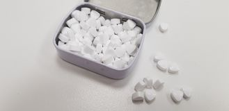 White candy spilled on a table near open metal box royalty free stock images