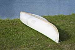 White canoe lay on green grass Stock Photo