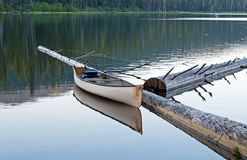White Canoe Reflecting on The Lake. A canoe sits quietly on a lake and reflects it's image stock photo