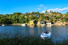 White Canoe Resting in Summer. Beautiful summer landscape with a white canoe resting in a sunny day with lake, houses and blue sky in background stock image