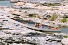 White canoe on rocky shore. White canoe on a ragged shoreline stock images