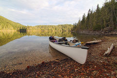 White Canoe Wilderness. A white canoe on the side of a Canadian lake with very calm water royalty free stock photography