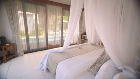 White canopy bed in room with swimming pool view. White canopy bed in bright room balinese style with glass door to swimming pool view behind curtain on sunny stock video
